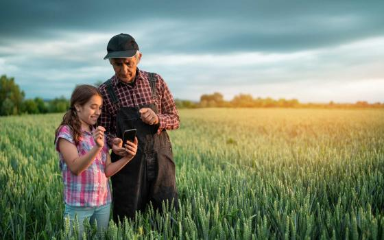 Farmer and granddaughter in a wheat field on a farm. The granddaughter is holding a mobile device and both are looking at it.